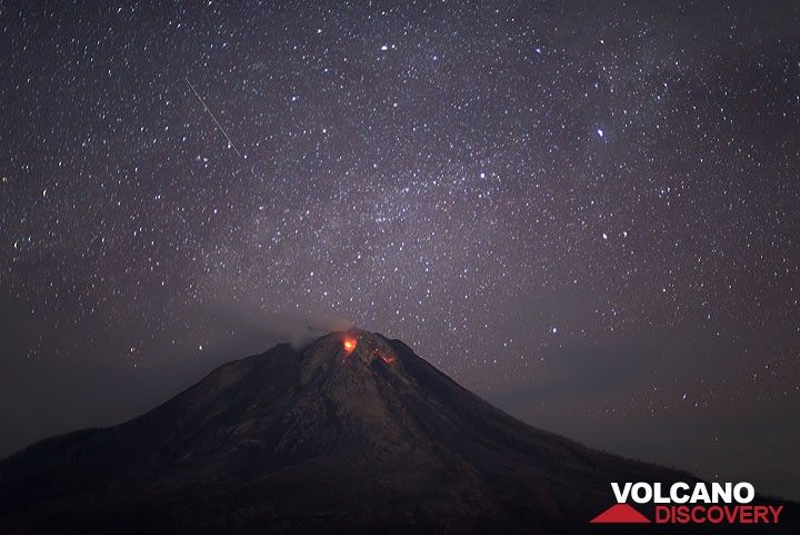 A meteor passes above Sinabung volcano with its two active lava lobes. (Photo: Tom Pfeiffer)