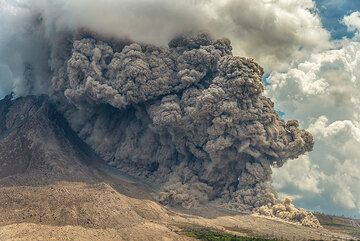 Ash plume from the pyroclastic flow rising and penetrating a cumulus cloud. (Photo: Tom Pfeiffer)
