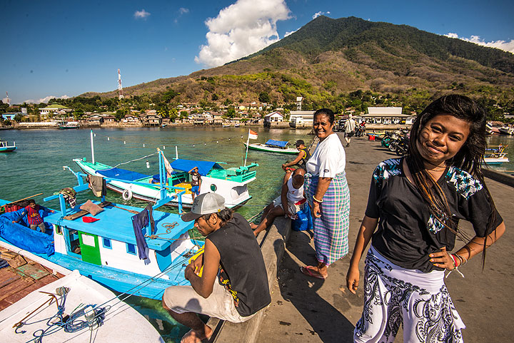 A girl poses for a picture in the harbour of Larantuka. Extinct Ile Mandiri stratovolcano in the background. (Photo: Tom Pfeiffer)