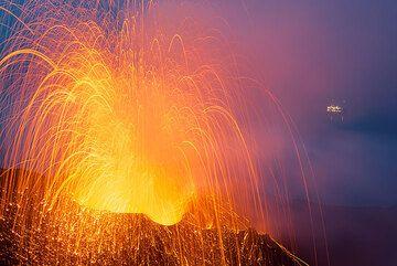 Erupción relativamente grande del respiradero del NW, las luces de un turista del barco en el fondo. (Photo: Tom Pfeiffer)