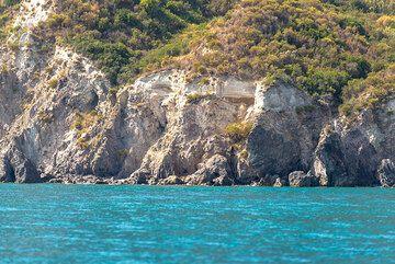 Monte Pilato's white pumice overlying older volcanic deposits along the coast (Photo: Tom Pfeiffer)