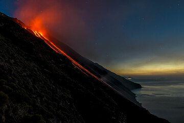 Night over Stromboli's Sciara del Fuoco - the distant island of Salina in the background. (Photo: Tom Pfeiffer)