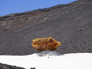 An old lava bomb on ice at the summit craters of Etna volcano. (Photo: Tobias Schorr)