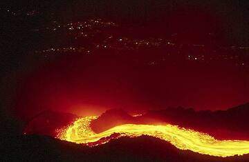 Lava flow at night and lights of Giarre in the background (Etna volcano) (c)