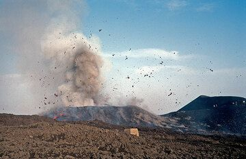 While many lava bombs are still flying (some into my direction), the heaviest ones have landed on the flanks of the new crater-cone, whirling up dust. (Photo: Tom Pfeiffer)