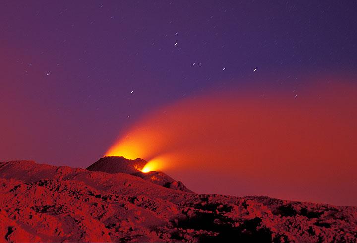 25. Juli. Ein kleiner Kegel, ca. 10 Meter hoch, hat sich über der Ausbruchsspalte bei etwa 2700 m Höhe gebildet. Das rote Umgebungslicht kommt von den Ausbrüchen des Cono del Lago auf 2500 m Höhe. (Photo: Tom Pfeiffer)
