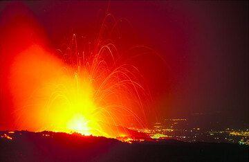Nächstliche Explosion des neuen Kraters. Einige Bomben fliegen bis zu 1 km hoch durch die Luft... Die Lichter von Catania im Hintergrund. (Photo: Tom Pfeiffer)