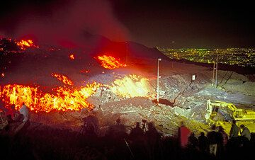 Media, lava watchers and a bulldozer at work against the menacing lava flow. Lights of Catania in the background. (Photo: Tom Pfeiffer)