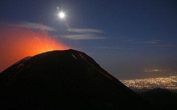 Strombolianische Tätigkeit vom Südostkrater im Oktober 2006. Die Lichter von Catania im Hintergrund. (Photo: Tom Pfeiffer)