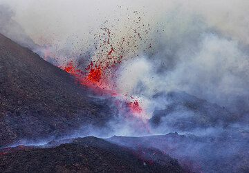 The lava fountain increases and a second vent opens up a few meters down along the fissure. The lava flow branches into two arms.  (Photo: Tom Pfeiffer)