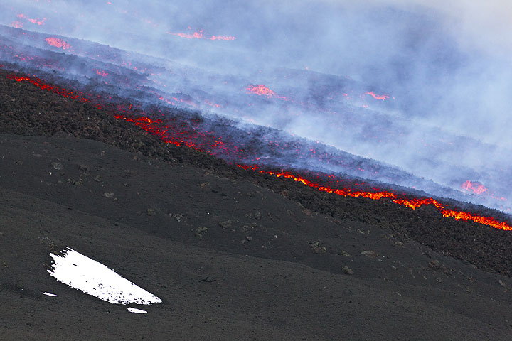 A patch of snow from the previous cold night and the edge of the lava flow from the eruption. (Photo: Tom Pfeiffer)