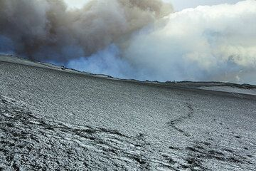 People have walked to the rim of the Valle del Bove, to see the lava flow. Clouds, ash and gas draw dramatic shapes into the sky above Valle del Bove. (Photo: Tom Pfeiffer)