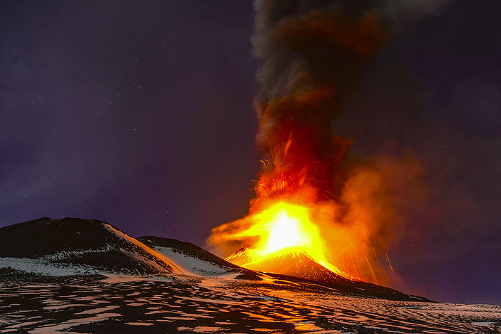 The bright glow illuminates the partially snow-covered surfaces of the mountain. The 2002 eruption cones to the left of the image. (Photo: Tom Pfeiffer)