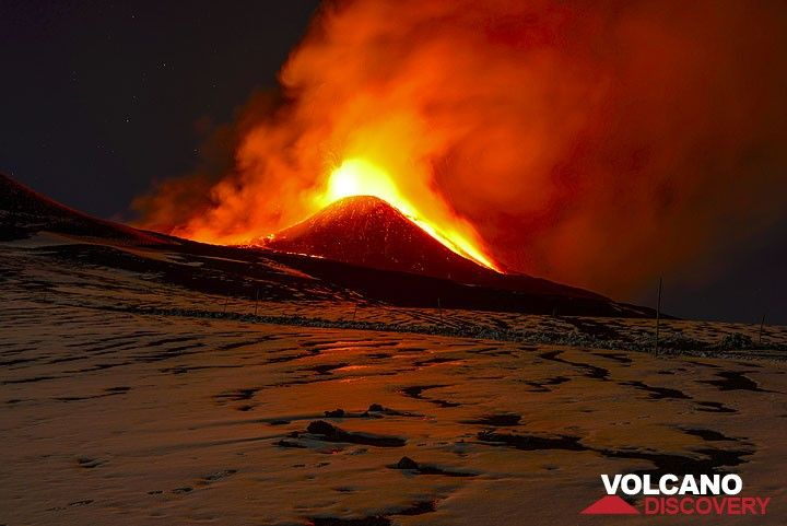 A lava flow erupts from the eastern flank of the cone. Red glow is mirrored on the icy surface in front of me. (Photo: Tom Pfeiffer)