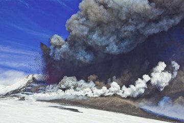 The lava fountain is now well over 300 m high and the ash plume rises several km. The lava flow from the saddle vent meets fresh snow and produces a white steam plume at the base of the cone. (Photo: Tom Pfeiffer)