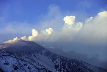 The next afternoon (12 Nov), the upper slopes of Etna are all white with snow. The main phase of the paroxysm is over, but explosions every minute or so continue at the NSEC. Interestingly, many of them produce steam rings, often in a row. (Photo: Tom Pfeiffer)