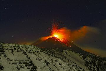 Tall strombolian explosion at the New SE crater and the snow-covered eastern headwall of the Valle del Bove in moonlight. (Photo: Tom Pfeiffer)