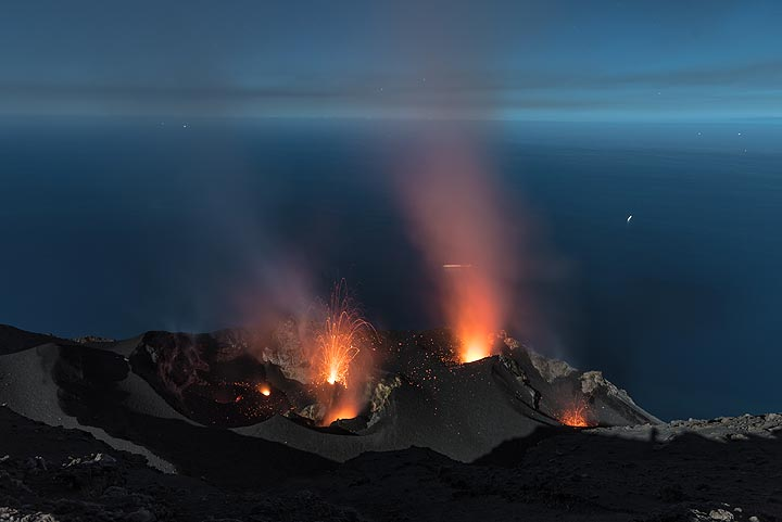 Moonlight illuminates the crater terrace (9 June 2017 night); a rare eruption occurs from the northern central vent (the only one observed during many hours). (Photo: Tom Pfeiffer)