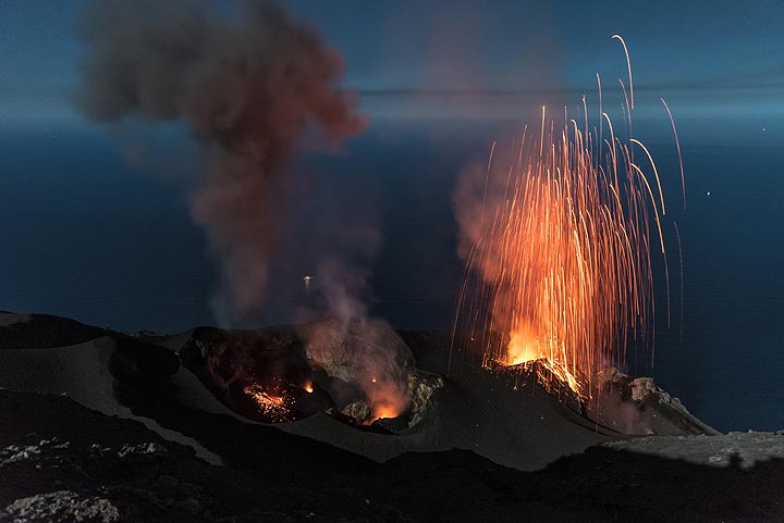 The westernmost (left) vent (S1) has produced an ash-rich eruption; glowing spatter still lies around this vent, which today was not often active (but becomes protagonist a few days later). Seconds later, a dry strombolian eruption occurred from the NE vent (right). (Photo: Tom Pfeiffer)