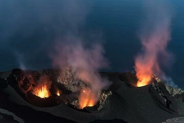 A small eruption occurs from the westernmost vent (S1), which is located in a wide pit. At the same time, weak spattering can be seen at the central crater (lower center). Spattering also is frequently seen at the eastern main vent (r). (Photo: Tom Pfeiffer)