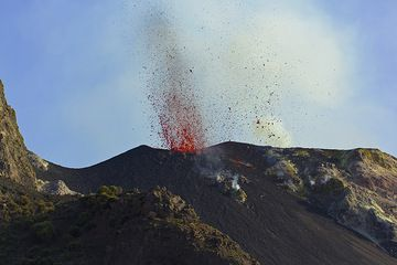 Eruption of the SE crater seen from the 400m viewpoint. The lava is glowing red in full daylight - quite unusual at Stromboli! We're excited to climb further up... (Photo: Tom Pfeiffer)
