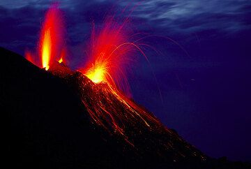 """Long exposure with strombolian eruption from NW vent and a """"smaller"""" eruption from the NE vent (r). (Photo: Tom Pfeiffer)"""