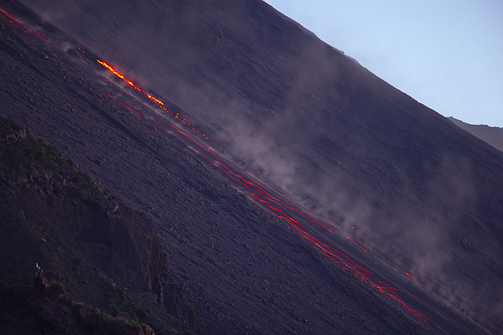 The weakly active front of the lava flow and trails of glowing rockfalls. (Photo: Tom Pfeiffer)