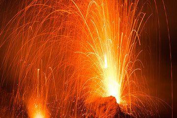 Pequeña erupción de una abertura en la base del hornito NW (cuya llama es visible detrás). (Photo: Tom Pfeiffer)