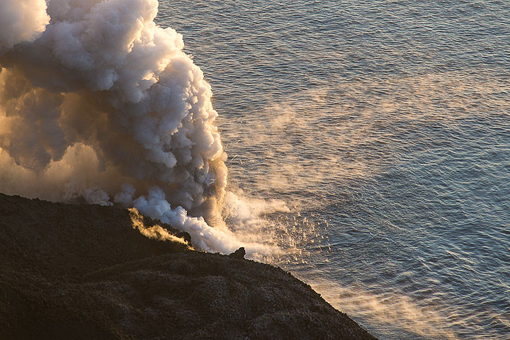 Littoral explosions sending hundreds of small bombs into the air to fall back like hail into the sea. Steaming hot surface water drifts in two directions away from the entry point. (Photo: Tom Pfeiffer)
