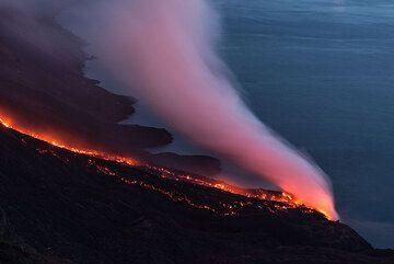 Lava flow illuminating the steam plume after night fall. (Photo: Tom Pfeiffer)