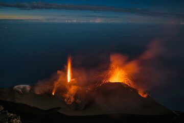As the blue hour is over, moonlight starts to lit the crater terrace where the north vent begins to send a noisy jet of lava into the air. (Photo: Tom Pfeiffer)