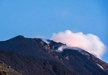 The crater area seen from the Sciara del Fuoco viewpoint in the early evening twilight. A small eruption is taking place from the western vent. (Photo: Tom Pfeiffer)