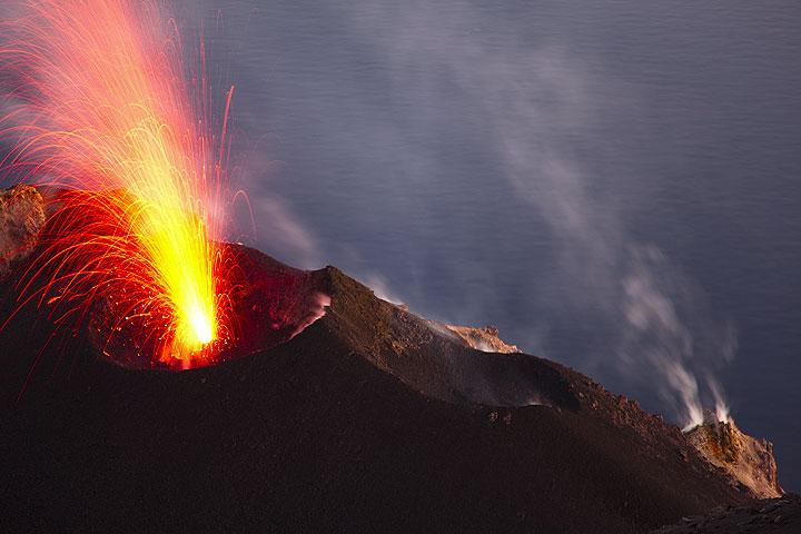Ein kerzenartiger Ausbruch vom oberen Schlot des NE Kraters. Rechts im Bild rauchende Fumarolen am äußeren unteren Kraterrand. (Photo: Tom Pfeiffer)