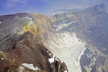 Walls of active craters are always very unstable. Debris has already deposited on the one-day old snow on the lower terrace inside the crater.  (c)