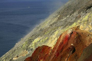 Yellow sulphur deposits and red oxides are abundant on the upper slope and rim of Fossa volcano. (Photo: Tom Pfeiffer)