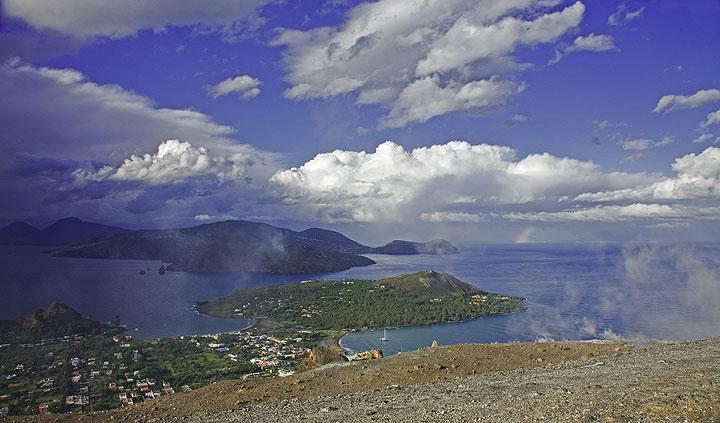Ein schöner Panoramablick von Vulcano über die Äolen. Unter uns ein Teil von Vulcano und die Halbinsel des Vulcanello, dahinter von links: Salina, Lipari, Panarea in der Nähe des Regenbogens, und ganz in der Ferne Stromboli. (Photo: Tom Pfeiffer)
