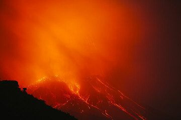 Red illuminated cloud engulfing the crater of Stromboli during an eruption (Photo: Tom Pfeiffer)