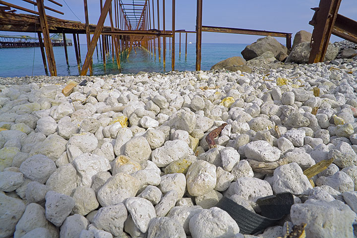 Pumice pebbles and old rusted structures of piers at the pumice quarry on Lipari  (Photo: Tom Pfeiffer)