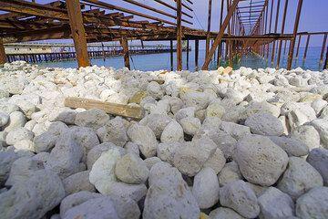 Bimssteinkiesel am Strand unterhalb der alten rostigen Verladestellen bei den Bimsseinbrüchen von Lipari.  (Photo: Tom Pfeiffer)