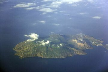 Aerial view of Vulcano Island. The left older part of the island is an older caldera - the remnant of a dissected stratovolcano, the right part is a younger caldera where the present-day harbour and tourist village of Vulcano is located next to the active cone (light brown) La Fossa. A narrow land bridge connects the island with the peninsula formed by the little cone Vulcanello (an island, that appeared in Roman times), mostly out of the right frame in this picture. (Photo: Tom Pfeiffer)