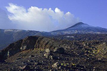Wir sind auf der NO-Riftzone des Ätna angelangt. Links von uns ein Pitkrater, ein paar hundert Meter oberhalb der noch rauchende obere Teil der Ausbruchsspalte vom Oktober 2002, und im Hintergrund der Kamm der Pizzi Deneri und der gewaltig dampfende Nordostkrater. (Photo: Tom Pfeiffer)