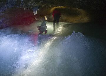 Ines and Rosario in the cave, looking at some ice stalactites. A mountain-like stalacmite is in the right foreground, caused by accumulation of dripping and freezing water drops onto the same spot.  (Photo: Tom Pfeiffer)