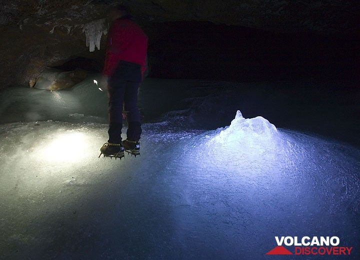 Rosario with his crampoons standing on the ice inside the cave. My torch illuminates a mound of ice formed by drops of freezing water from the ceiling. (Photo: Tom Pfeiffer)