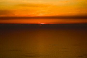 Glowing orange sky and the setting sun behind a layer of mist on the horizon (Photo: Tom Pfeiffer)