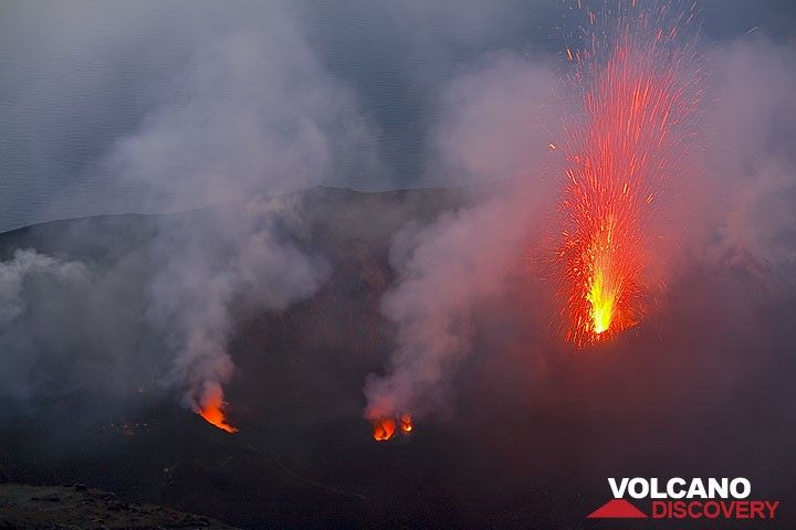 Glowing, spattering vents of the central crater and a bright eruption from the western vent of the NE crater (Photo: Tom Pfeiffer)