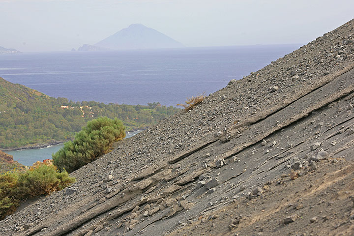 The flank of the Fossa cone, covered by ash, sand and blocks from the eruptions in 1888-1890. Stromboli in the hazy background. (Photo: Tom Pfeiffer)