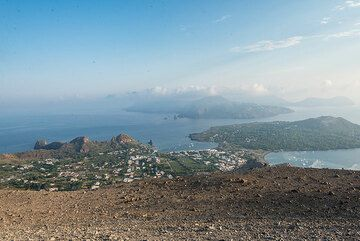 View from Fossa onto Vulcano village, Vulcanello peninsula, and Lipari in the background. The summits of Salina's volcanoes just peak out of the cluod layer in the distance (left). (Photo: Tom Pfeiffer)