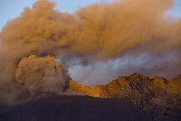 First sunrays illuminate the ash plume from Showa crater. (Photo: Tom Pfeiffer)
