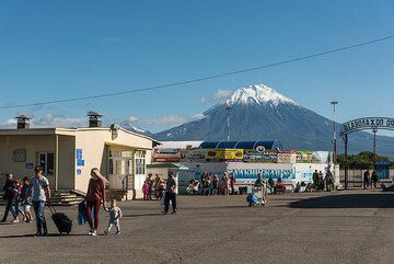 Arrived! People leave the small luggage delivery room of the airport and are greeted by unusually good weather with snow-capped Koryaksky volcano behind. (Photo: Tom Pfeiffer)