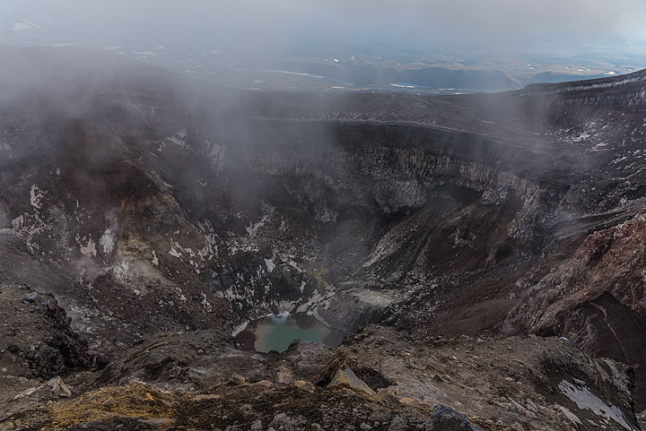 Mist hovers over the NW crater with its turquoise lake. (Photo: Tom Pfeiffer)